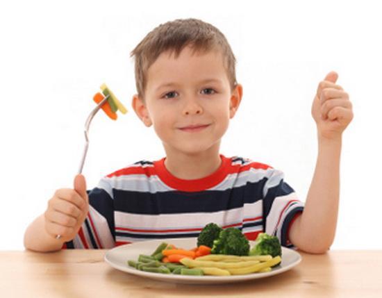 ребенок ест овощи на тарелке