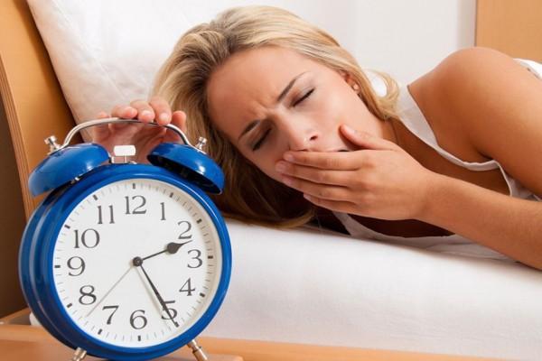 девушка сонная выключает будильник