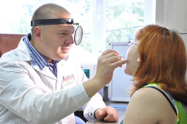 лор осматривает рот пациента