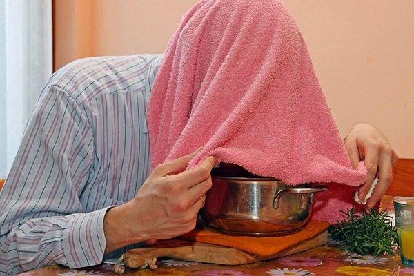 мужчина проводит ингаляцию картошкой