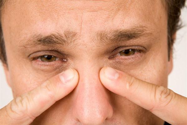 мужчина показывает пальцами на нос