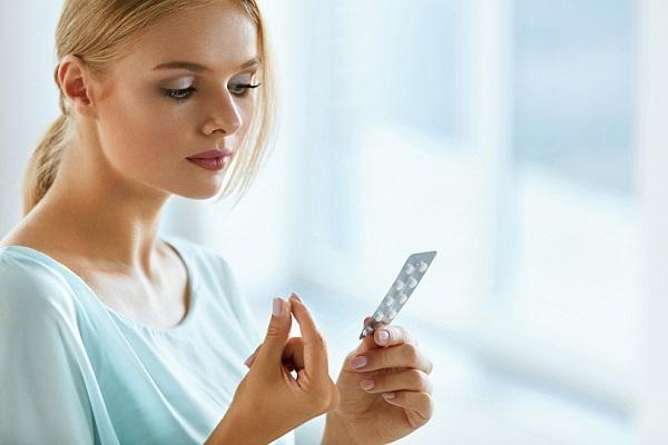 девушка смотрит на упаковку таблеток