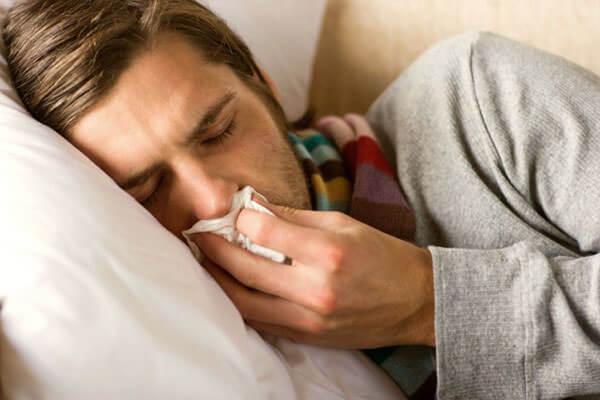 мужчина в кровати с насморком