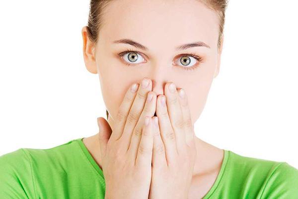 женщина закрывает нос руками