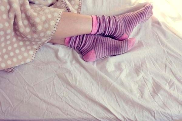 девушка в носках на кровати