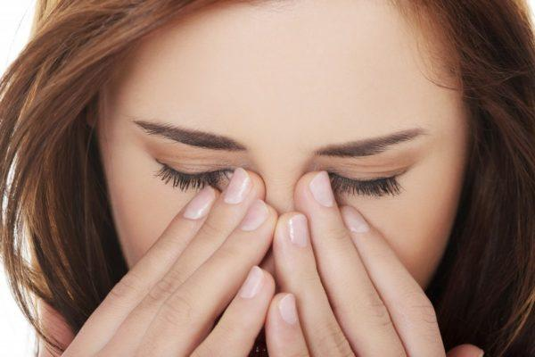 девушка закрывает свой нос