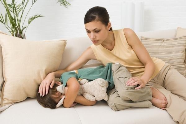 ребенок с головной болью на диване