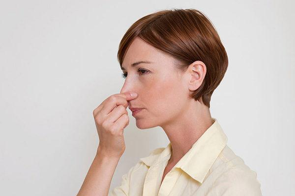 женщина держится за нос