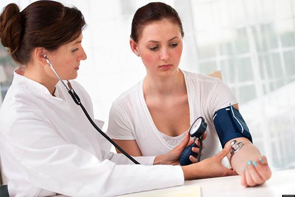 врач меряет давление у женщины