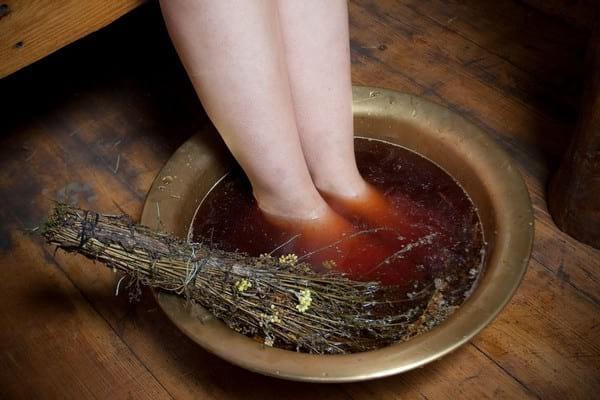 женщина парит ноги с травой