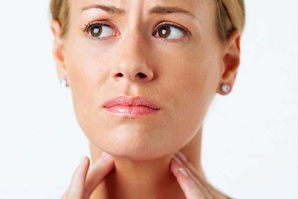 женщина держится за щитовидную железу