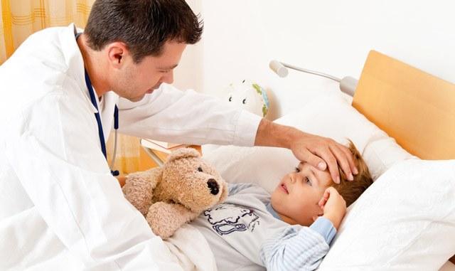 врач трогает лоб ребенку
