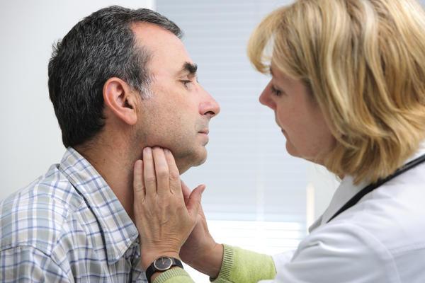 врач трогает щитовидную железу у мужчины
