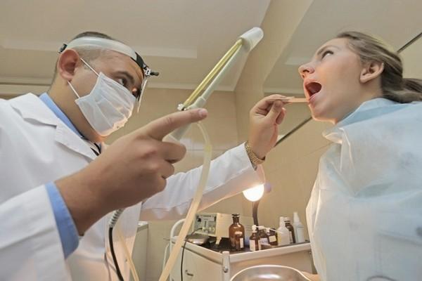 врач промывает миндалины пациенту