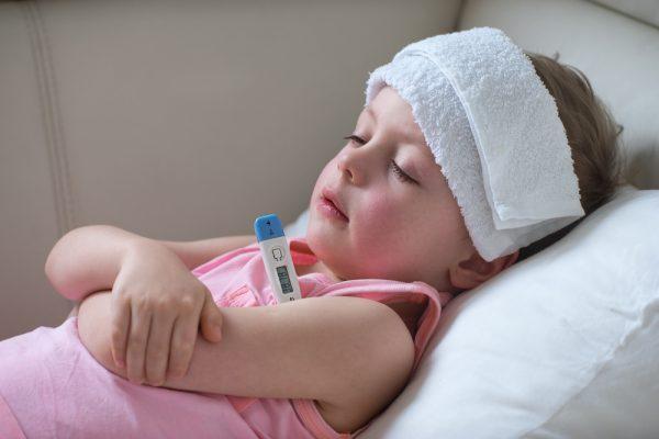девочка лежит в кровати с температурой