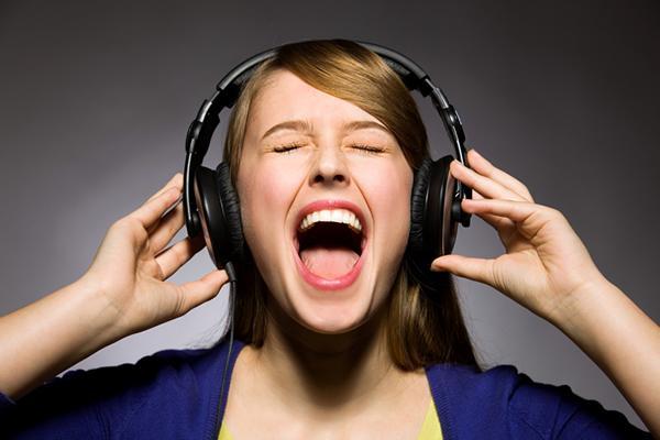 девушка слушает музыку в наушниках и поет