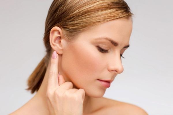 женщина показывает на ухо