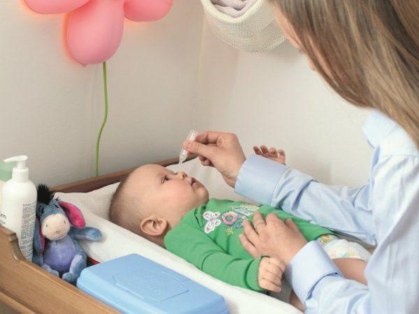 маленькому мальчику закапывают нос