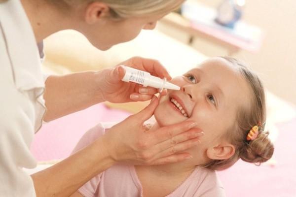 мама девочке закапывает нос